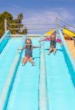 De leuke meisjes op water glijden bij aquapark tijdens Royalty-vrije Stock Fotografie