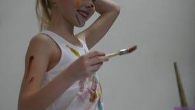 De leuke meisjeschilder trekt op de lijst en op zich aangaande haar kleren Langzame Motie stock video