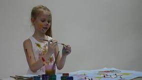 De leuke meisjeschilder trekt op de lijst en op zich aangaande haar kleren Langzame Motie stock footage