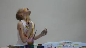 De leuke meisjeschilder trekt op de lijst en op zich aangaande haar kleren Langzame Motie stock videobeelden