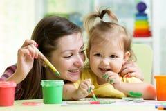 De leuke moeder onderwijst haar dochterjong geitje om te schilderen Royalty-vrije Stock Afbeeldingen