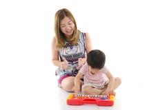 De leuke moeder onderwijst haar zoonsjong geitje om elektrostuk speelgoed piano te spelen Royalty-vrije Stock Afbeelding