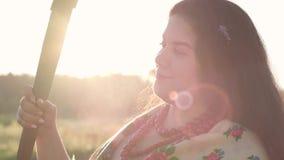 De leuke mollige vrouw die van het close-upportret een zeis op het groene de zomergebied houden in zonlicht Mooi landschap folklo stock video