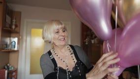 De leuke oma viert haar verjaardag Houdt multicolored ballons in haar handen stock videobeelden