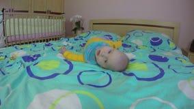 De leuke pasgeboren baby probeert omkeert zijn rug 4K stock video