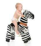 De leuke peuter van de kindbaby zit en berijdt groot gestreept paardstuk speelgoed Stock Afbeeldingen