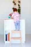 De leuke peuterbaby beklimt op stapkruk, die dingen op het hoge bureau in de keuken proberen te bereiken Stock Afbeeldingen