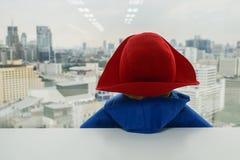 De leuke pop in blauwe sweater met rode hoed bekijkt buiten het venster royalty-vrije stock foto's