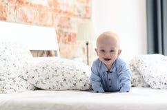 De leuke pret weinig jongen ligt op het ouder` s bed, het lachen en I Stock Foto's