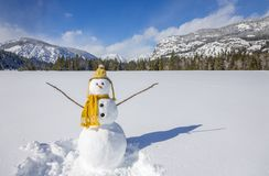 De leuke pretsneeuwman met breit hoed en sjaal in de sneeuwscène van het de winterlandschap met bergen en blauwe hemel royalty-vrije stock fotografie