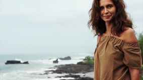 De leuke rijpe vrouw met bruin krullend haar bevindt zich bij klip en staart op zee golven stock video