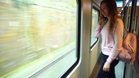 De leuke ritten van de meisjesreiziger leiden en geratel op telefoon op, die zich dichtbij groot vervoervenster bevinden stock footage
