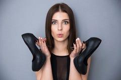 De leuke schoenen van de vrouwenholding over grijze achtergrond Stock Foto's