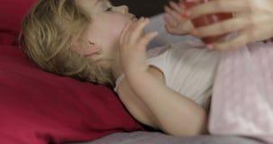 De leuke slaap van het babymeisje op comfortabel bed thuis en het drinken sap van fles stock videobeelden