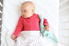 De leuke slaap van het babymeisje in voederbak, royalty-vrije stock afbeeldingen