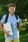 De leuke, slimme, jonge jongen in blauw overhemd bevindt zich op het gras met bol en schoolrugzak, werkboeken Onderwijs, terug na stock afbeelding