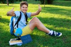 De leuke, slimme, jonge jongen in blauw overhemd zit op het gras met bol, werkboeken, bord en houdt zijn duimen in het park tegen royalty-vrije stock foto's