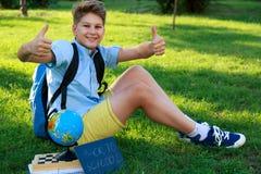 De leuke, slimme, jonge jongen in blauw overhemd zit op het gras naast zijn schoolrugzak, bol, bord, werkboeken Onderwijs stock foto