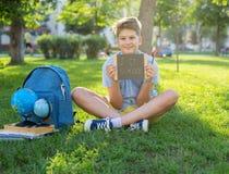 De leuke, slimme, jonge jongen in blauw overhemd zit op het gras naast zijn schoolrugzak, bol, bord, werkboeken Onderwijs stock fotografie