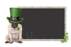 De leuke slimme pug puppyhond met st Patrick ` s van de daghoed en pijp zitting naast leeg bord ondertekent met klaver en hoef Royalty-vrije Stock Afbeelding