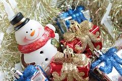 De leuke sneeuwman, de doos van Kerstmisgiften of stellen en Santa Claus-het huis op gouden wimpel of klatergoudachtergrond voor Royalty-vrije Stock Fotografie