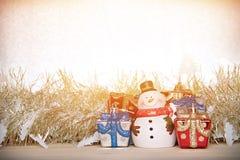 De leuke sneeuwman, de doos van Kerstmisgiften of stelt voor en de gouden wimpel of het klatergoud op hout, zilver schittert acht Royalty-vrije Stock Fotografie