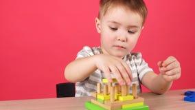 De leuke spelen van de peuterjongen in thuis het ontwikkelen van spel Peuteractiviteiten voor kinderen Vroege kinderjarenontwikke stock videobeelden