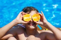 De leuke sportieve jongen zwemt in de pool met doughnutring en heeft pret, glimlacht, houdt sinaasappelen vakantie met jonge geit stock fotografie