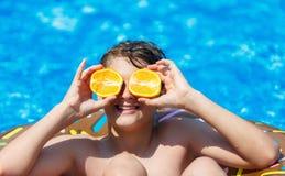 De leuke sportieve jongen zwemt in de pool met doughnutring en heeft pret, glimlacht, houdt sinaasappelen vakantie met jonge geit royalty-vrije stock foto