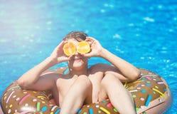 De leuke sportieve jongen zwemt in de pool met doughnutring en heeft pret, glimlacht, houdt sinaasappelen vakantie met jonge geit royalty-vrije stock afbeeldingen