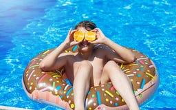 De leuke sportieve jongen zwemt in de pool met doughnutring en heeft pret, glimlacht, houdt sinaasappelen vakantie met jonge geit stock foto's