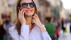De leuke student in zwarte sunglassesingang in de straat en de bespreking op haar cel telefoneren stock footage