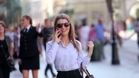 De leuke student in zwarte sunglassesingang in de straat en de bespreking op haar cel telefoneren stock video