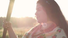 De leuke te zware vrouw die van het close-upportret een zeis op het groene de zomergebied houden in zonlicht Mooi landschap stock video