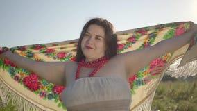 De leuke te zware vrouw heft handen op houdend traditionele sjaal op de zomergebied in zonlicht Mooi landschap stock footage