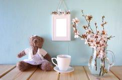 De leuke teddybeer, de kop van koffie en het lege kader naast de lente witte kers komen boom tot bloei Royalty-vrije Stock Foto
