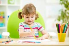 De leuke tekening van het kindmeisje met kleurrijke potloden Stock Foto