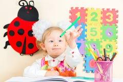 De leuke tekening van het kindmeisje met kleurrijke potloden en viltpen bij lijst in kleuterschool Stock Afbeeldingen