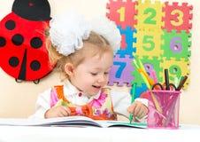 De leuke tekening van het kindmeisje met kleurrijke potloden en viltpen in kleuterschool bij lijst Stock Foto's
