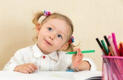 De leuke tekening van het kindmeisje met kleurrijke potloden en viltpen in kleuterschool in kleuterschool Royalty-vrije Stock Afbeelding