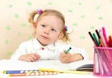 De leuke tekening van het kindmeisje met kleurrijke potloden en viltpen in kleuterschool in kleuterschool Stock Foto's