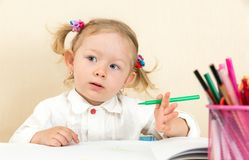 De leuke tekening van het kindmeisje met kleurrijke potloden en viltpen in kleuterschool in kleuterschool Royalty-vrije Stock Foto's