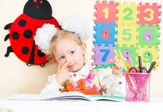 De leuke tekening van het kindmeisje met kleurrijke potloden en viltpen in kleuterschool in kleuterschool Stock Foto