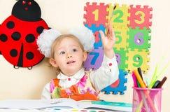 De leuke tekening van het kindmeisje met kleurrijke potloden en viltpen in kleuterschool in kleuterschool Royalty-vrije Stock Fotografie