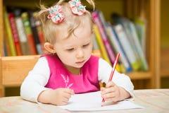 De leuke tekening van het kindmeisje met kleurrijke potloden in kleuterschool bij lijst in kleuterschool Royalty-vrije Stock Foto