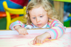 De leuke tekening van het kindmeisje trekt het ontwikkelen van zand in kleuterschool bij lijst in kleuterschool Royalty-vrije Stock Foto