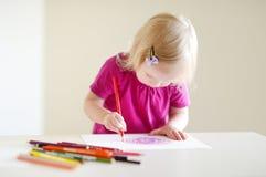 De leuke tekening van het peutermeisje met kleurrijke potloden Stock Afbeelding