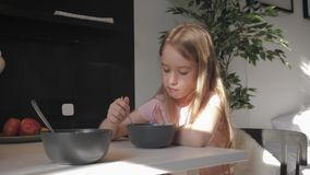 De leuke tiener zit bij de dinerlijst en het eten van havermoutpap voor concept van de ontbijt het Gezonde levensstijl stock footage