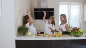 De leuke twee zusters en hun mooie moeder met lang haar in witte kleren geven elkaar hoogte vijf terwijl stock video