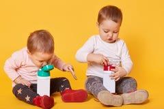 De leuke tweelingzusters hebben samen een maaltijd zonder ouders, spelen met elkaar, doorbrengen vrije tijd Één van de zusters wi royalty-vrije stock afbeeldingen